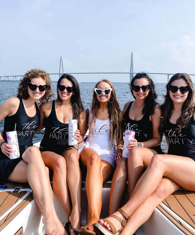 Girls taking a boat tour in the Charleston harbor with the Ravenel bridge in the background.