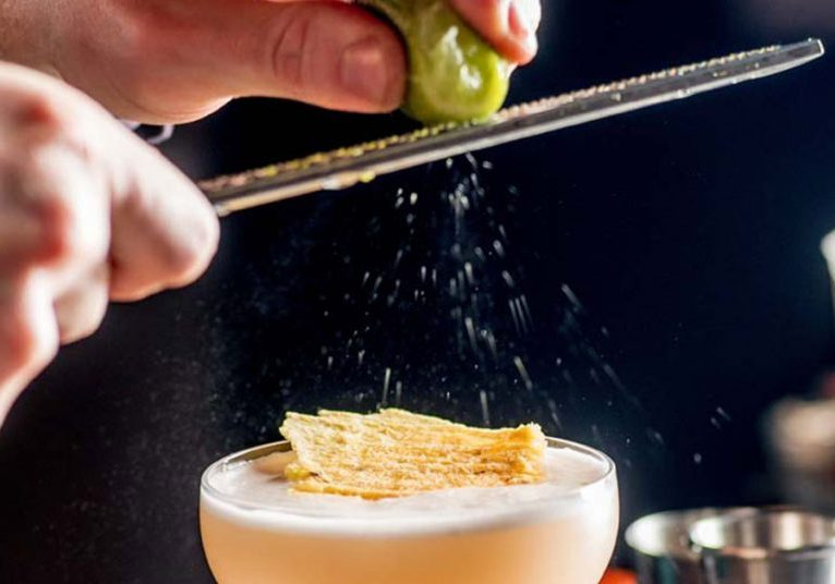 barman rubs lime zest on cocktail. bartender is preparing a cocktail for serving.Finishing a Cocktail. Mixology