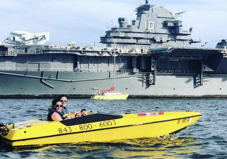 Couple rents a speedboat in Charleston—pose in front of the YSS Yorktown.